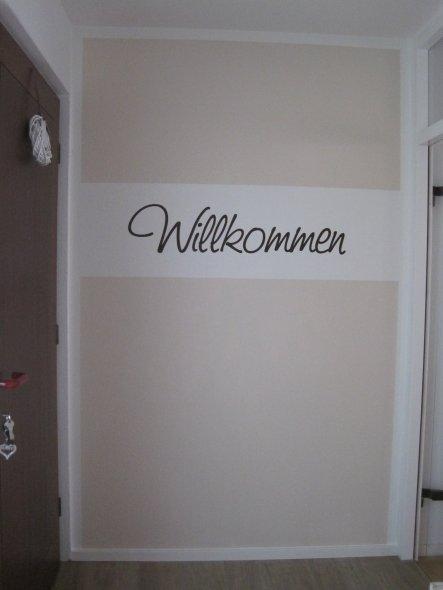 Wand,hinter der Eingangstür, die man vom WC aus sieht.