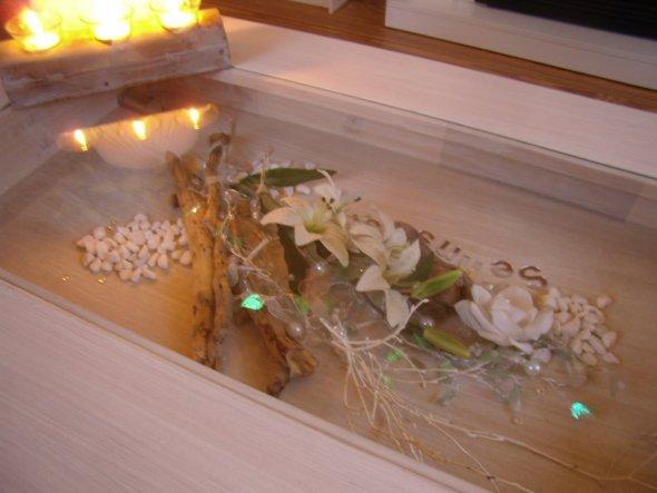 In den Tisch mit Schublade habe ich Treinholz gesammelte Steine Blüten und eine Lichterkette dekoriert