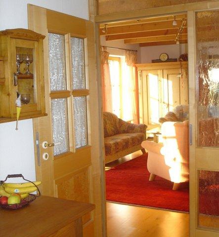 Wohnzimmer mit Holzbalkendecke und Parkett.Vier bodentiefe Sprossenfenster und noch zwei Türen und ein Kachelofen. Nicht einfach die Möbel zu stellen