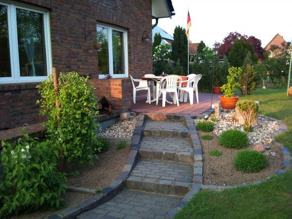 Die Terasse wir grade umgebaut. Das Blumenbeet muß einem Teich weichen :o)Und neue Möbel kommen auch dazu.