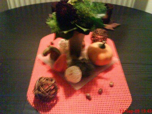 Glasschale mit kleinem Dhalienstrauß, einem Zierkürbis, kleinen Keramikkürbissen, Eicheln und Rattankugeln.