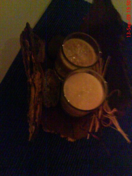 Ein Stück Baumrinde, 2 Gelkerzen in beige und creme, eine handvoll Flusskiesel und Sisalband.