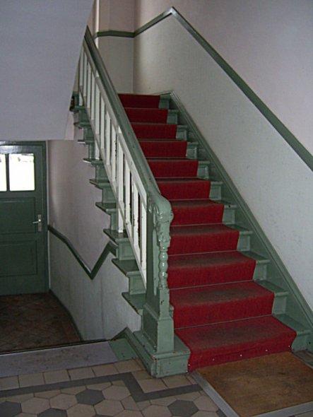 Blick zum Hintereingang und ins Treppenhaus. Die Wände sind unterhalb der Holzleiste tapeziert, oberhalb verputzt.