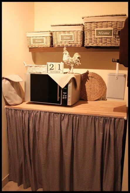 Hinter dem Vorhang (selber genäht) versteckt sich die Waschmaschine und ein kleiner Gefrierschrank. In den Körben befinden sich Waschpulver und