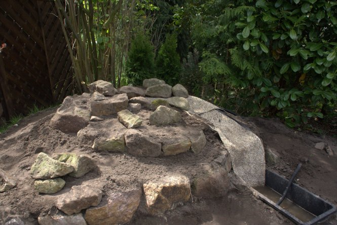In die Erde eingelassen haben wir eine Maurerwanne mit Bachlaufpumpe (von Oase);  der Pumpenschlauch verschwand unter der Erde. Die Wanne ist mit eine