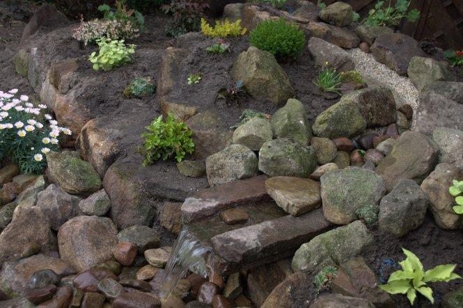 als Ausfluss dient eine Steinplatte, die wir einfach mit zwei langen Steinstücken links und rechts versehen haben, so dass das Wasser schön in die Wan