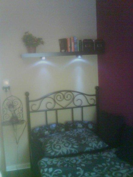 Das ist mein Bett, darüber ein Wandregal.