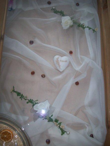 ein Organza in die Tischschublade, Rosengesteck, ein Herz und ein paar braune Glasnuggets und fertig ist der Tisch