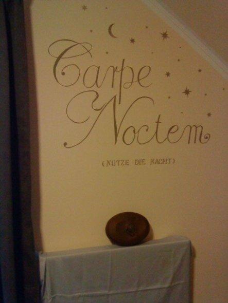 Hier hab ich mit ein bisschen restlicher Farbe einen Schriftzug auf die Wand gepinselt. Auf dem verhüllten Heizkörper liegt eine alte Kupferwärmflasch