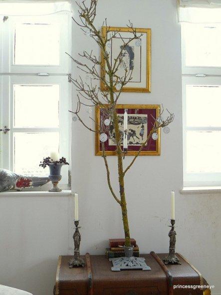 Ein knorriger Hollonderast in einem WEihnachtsbaumständer - dekoriert mit antiken Ziffernblättern und einem antiken Kerzenhalter, wie sie früher in de