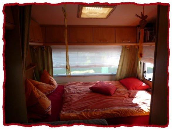 Auch hier kann man die grünen Gardinen sehen... rechts ist ein Kleiderschrank mit Doppeltür und an der Seitenwand zum Bett haben wir einen Fern