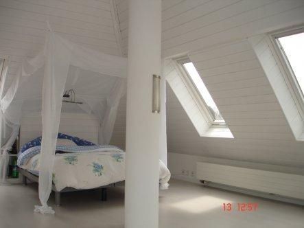 Blick von der Treppe aufs Bett. Der Kamin mitten im Raum liess sich leider nicht herausnehmen, weiss gestrichen sieht es wie eine Säule aus