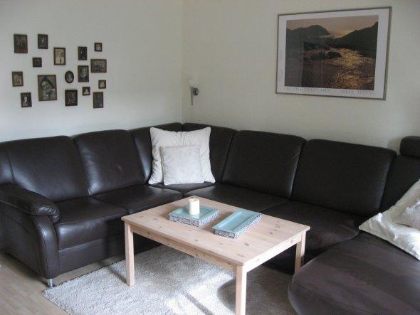 Unsere Couch mit gewachstem Tisch. Die Bilder links ist meine Ahnengalerie. Da hab ich alle alten schwarz/weiß Fotos von früher aufgehängt.