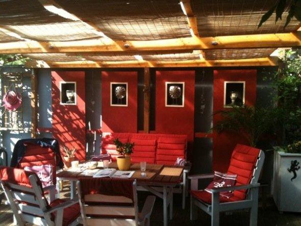 2010 habe ich die Garagenwand des Nachbarn grau und rot bemalt. Wir haben dann in Pressholplatten Nischen aus Hozkisten eingebaut - alles wurde farbig