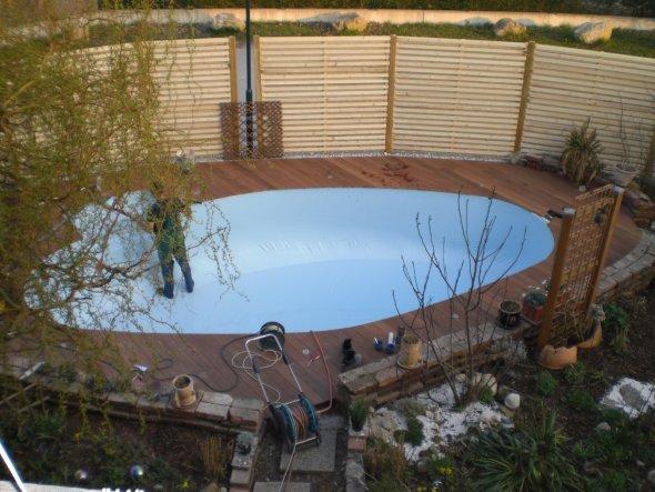 Zaun haben wir aufgestellt und Holzdeck ist verlegt. Nun wird die Poolfolie angebracht.