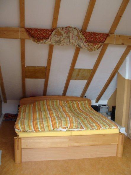 ...auf's Bett ohne Himmel.  Der Abstand zwischen Bett und Kniestock ist mit einem eingepassten Holzkasten überbrückt. Darin eingelassen