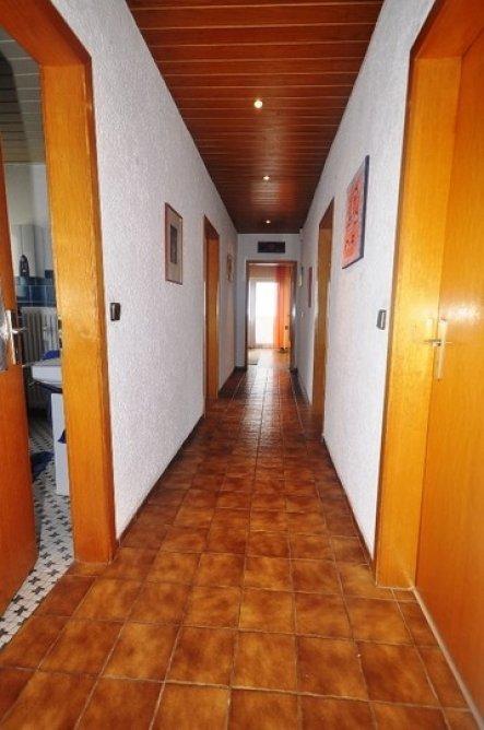 Der lange lange dunkle Flur. Oben dunkles Holz, unten dunkle Fliesen. In diesen Raum gelangt Tageslicht wenn man die Zimmertüren offenlässt. In der De