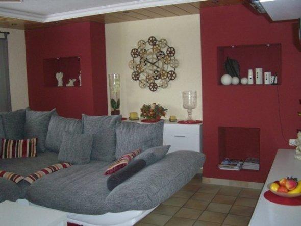 Hinter der Couch verbirgt sich eine Hängekommode.  Seitlich die roten Säulen sind aus glatten Gipskarton aufgebaut.  Zwei Fächer mit ind