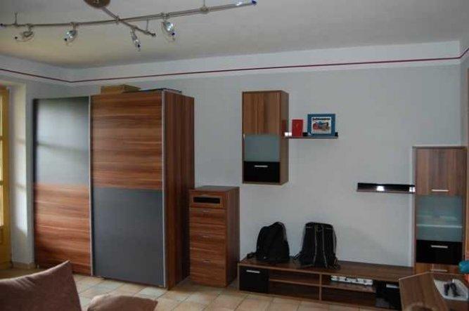 Graue Wände und eine cyclamfarbene Bodüre bieten einen schönen Kontrast zu den dunklen Möbeln.