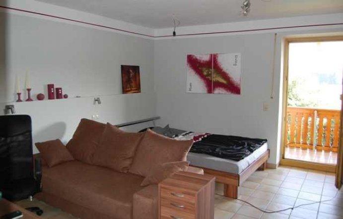 Das Bett versteckt hinter der Couch. Auch von hier muß der Blick zum TV möglich sein.  An der linken Wand einen Sockel auf dem etwas Deko plazi