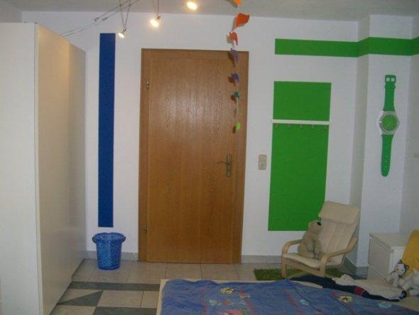 Gegenüber dem Schrank ist die Garderobenleiste und Leseecke in hellen grün.