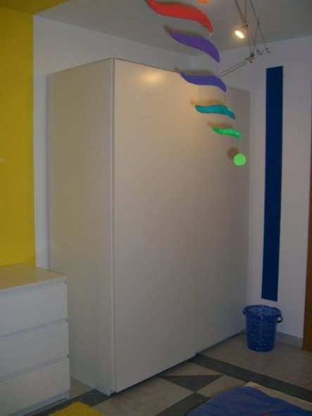 Diagonal zum blauen Schreibeck ist die blaue Ankleideecke.  Ein Pax bietet genügend Stauraum und ein blauer Eimer ist der Wäschekorb.