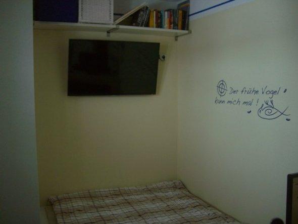 Über dem Fussende vom Bett findet der TV hängend Platz, darüber auf dem Wandbord verschwinden die Bücher.