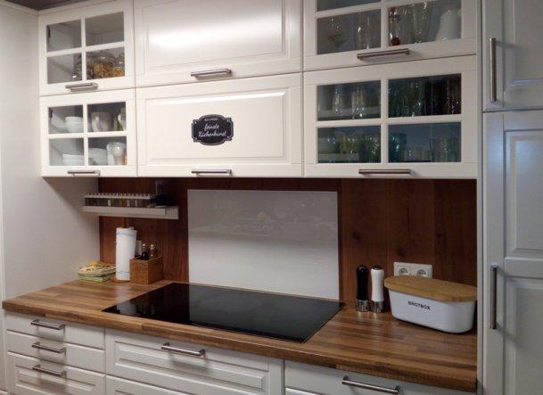 Die Kochnische haben wir mit Vinyllaminat verkleidet. MIttig als Spitzschutz hinter dem Induktionskochefeld eine weiße Glasplatte geklebt.