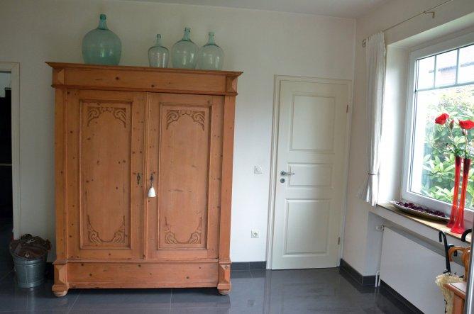 Der Schrank war mal dunkelbraun. Nun dient er als Garderobe. Hinter der Tür rechts ist das Gäste-WC.