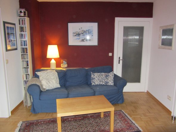 Unser blaues Sofa... vor der roten Wand. Die Ablage/Sideboard ist ein weißes Brett aus dem Bumarkt, schief abgesägt. Das Sofa hätte gerade nicht an di
