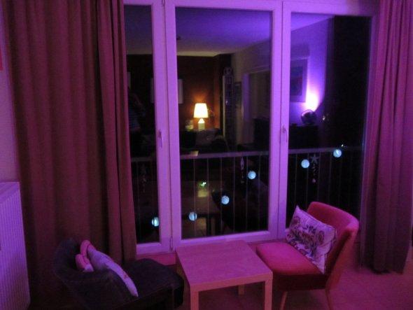 Abendansicht: Die Fensterfront mit zwei Vintage-Sesseln in Samt. In den Fenstern hängt noch die Sommerdeko: Solar-Lampions.. Dicke Samtvorhänge in bei