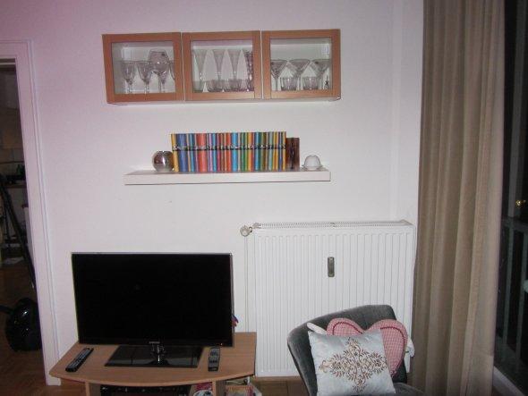 Die Wand ist aufgrund der Heizung nur schwer zu nutzen gewesen. Die Vitrine hat einen weißen Korpus und drei Türen in Buche. Ein drehbarer Fernsehtisc