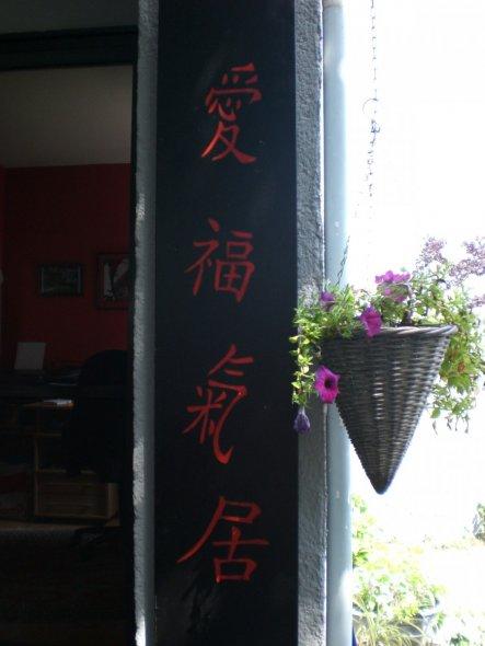 Eine chinesische Beschriftungstafel ist am Eingang angebracht.