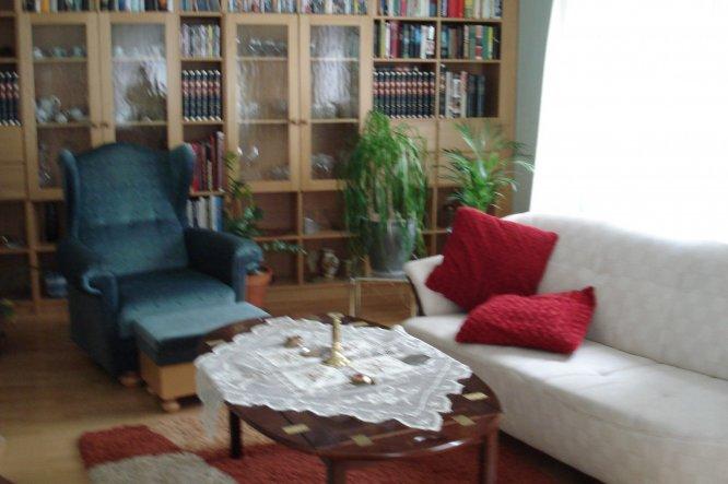 Unser Wohnzimmer ist mit einer  Bücherwand und mit einem großen  Kacheloffen ausgestattet. Das Sofa und der Ohrensessel sind zum sitzen bez. liegen se