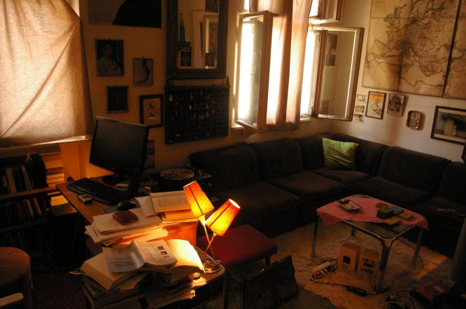die Wohn-ecke des Zimmers. 70er-Jahre-Couch mit Glastisch.