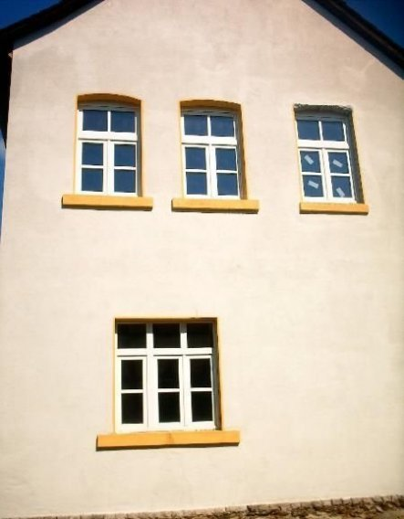 Ansicht auf die Südseite des Gebäudes. Dies ist auch die Wetterseite. Jahrelange Witterungseinflüsse haben die seinerzeit aus Holz hergestellten Fenst