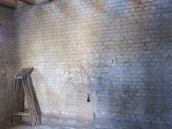 Doppelte Kalksandsteinmauer innenbelüftet; dennoch ist der Putz abgefroren. Die Öffnung in der Wand stellte den Durchbruch für das Abwasser des Küchen