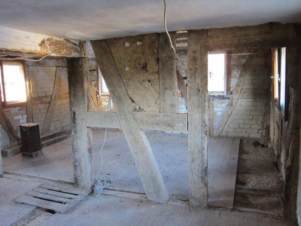 Großes Schlafzimmer rechts vom Flur abgehend. Die alten Holzdielen rechts im Bild mussten vor der Fassadenerneuerung hochgenommen werden.  Der zentral