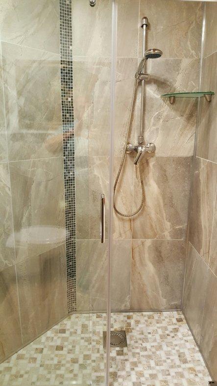 Duschtasse mit Marmor-Mosaik und große Wandfliesen grau, in Steinoptik