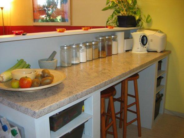 Als praktische Ergänzung zur grauen Einbauküche (vom Vermieter) bietet der Küchentresen viel Platz beim Zubereiten von Essen, eine Menge Stauraum und