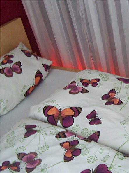 Die Unterbodenbeleuchtung unter dem Bett strahlt die weißen Gardinen heinauf