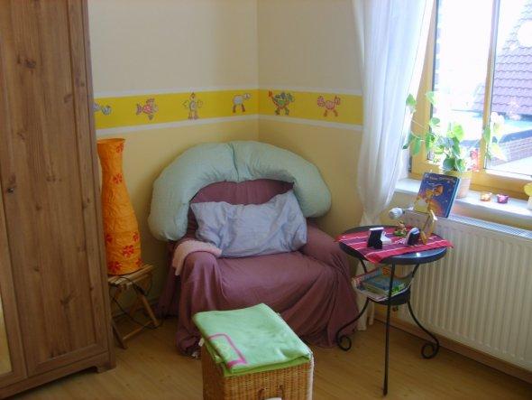 Ein gemütlicher Platz aus einem alten gut eingesessenen Sessel mit einem Überwurf mit Beistelltisch. Der Wäschekorb dient gleichtzeitig auch als Fußab