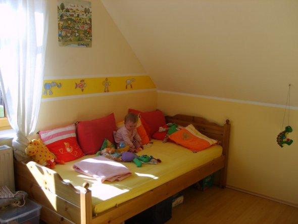 Das ehemalige Gästebett mit ein paar schönen Kissen und Kuscheltieren bestückt.
